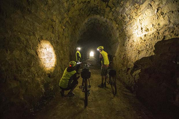 Cyclists follow the trail through the Rakis tunnel on the disused Windsor/Tokarahi railway line.