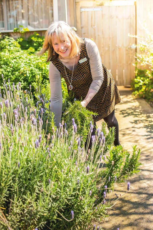 Bronwyn picking rosemary in the herb garden