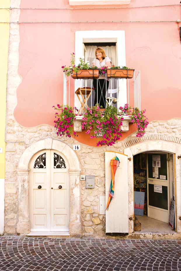 The flower-clad balcony off the bedroom is a place to watch the tapestry of life unfold in the Italian village where she lives for months each year.
