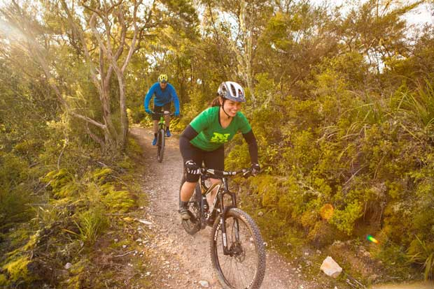 Nadia Coombe and Glenn Cullen explore the Te Ara Ahi – Thermal by Bike trail near Rainbow Mountain during a Rotorua mountain biking trip, Rotorua, New Zealand.